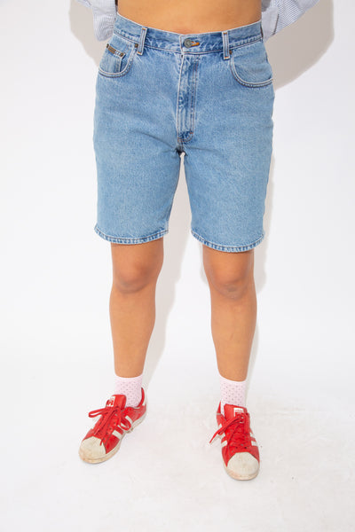 These Calvin Klein Shorts are mid-length and mid-wash blue. Branding on the front pocket, back pocket and button
