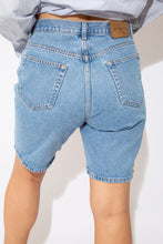 Load image into Gallery viewer, These Calvin Klein Shorts are mid-length and mid-wash blue. Branding on the front pocket, back pocket and button