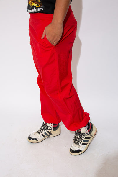 model is wearing red track pants that are made by Marlboro