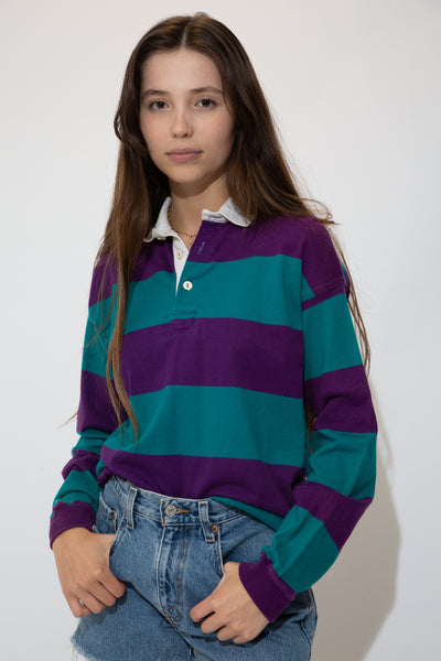 This soft, rugby style long-sleeved sweater is horizontally striped in purple and green with a white collar and matching white buttons.