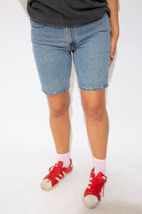 These Levis 505 denim shorts are midi-length and mid-wash blue. Branding on buttons and back of waistline.