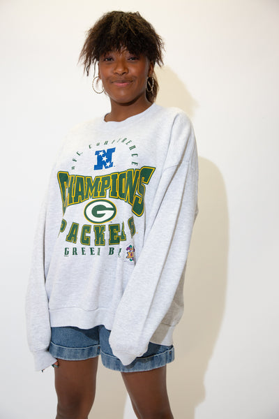 the model wears a grey sweatshirt with a green bay packers spell out on the front
