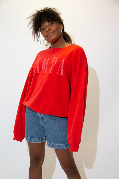 the model wears a red sweater with a 'Tampa' spell-out across the front