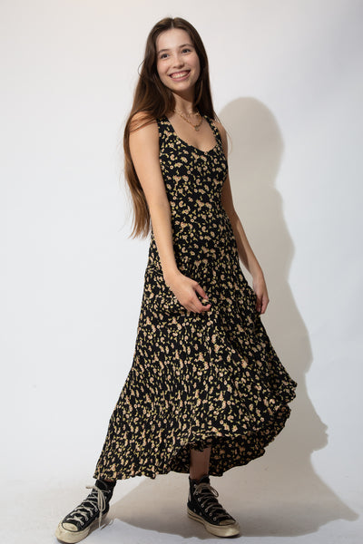 This vintage dress is black in colour with a full-length flowy fit, pale brown and green floral design, flattering neckline and a criss-cross back.