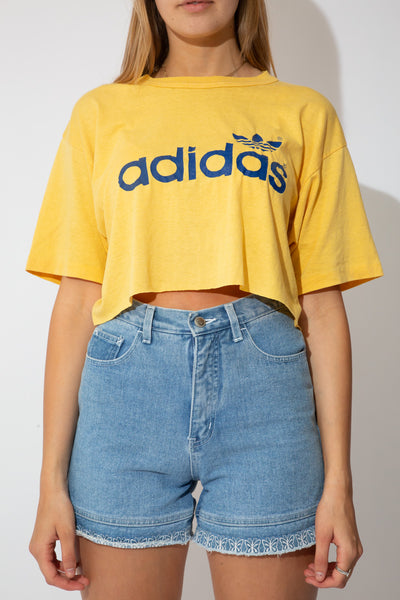 yellow cropped tee with large Adidas logo in blue on the front