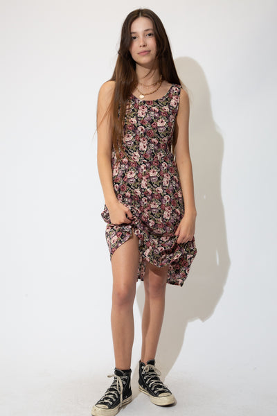 This summer dress is a mid-length fit with a pink, purple and green floral pattern and a criss-cross, lace-up back. Has a tailored waist, thick singlet straps and flowy skirt.