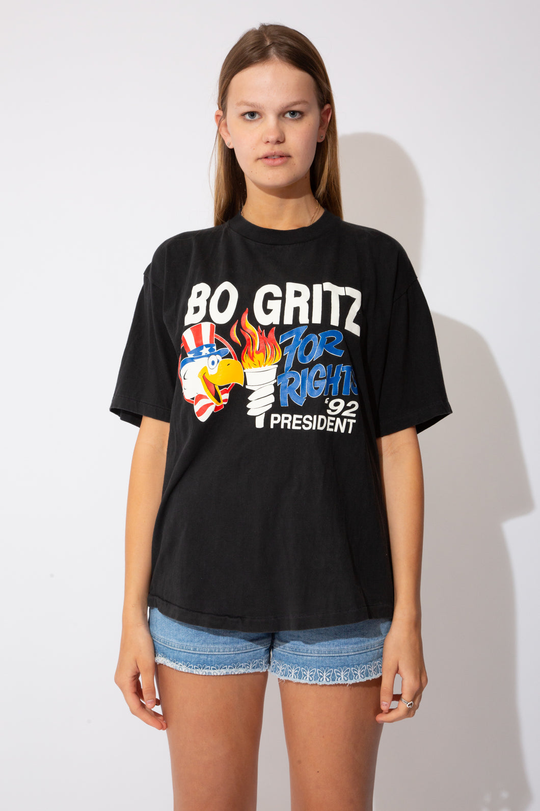 Black tee with Bo Gritz graphic on the front and an eagle holding a torch. On the back there is information about George Bush's new world order (which is clearly disagreed)