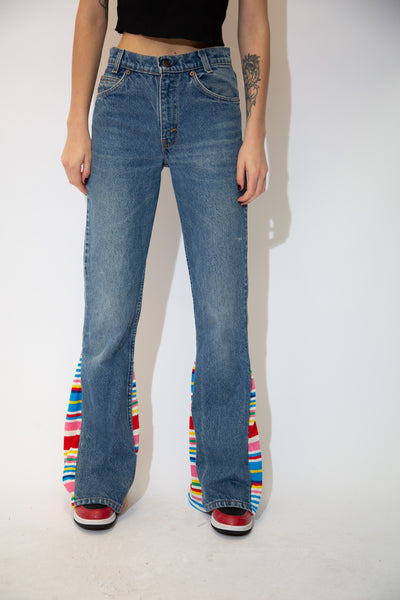 Mid-wash blue with a flared leg and mid-waist fit, these jeans have colourful striped bottoms that add a but of a spice to these easy fit jeans!
