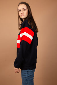 This All-American coloured sweater is navy blue with a large red and white stripe across the middle and is finished off with a closing zip and pockets. This fleece-like sweater is a Winter must-have!