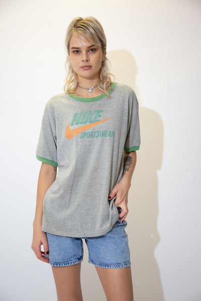 This grey tee is in a ringer style with a green rimmed collar and sleeves. 'Nike Sportswear' is printed across in green with an orange tick behind it.