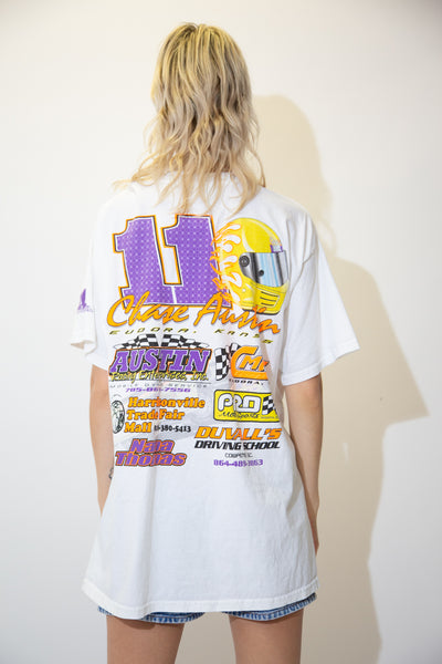 White tee with a large colour print of Chase Austin, his number 11 car and Sudora, Kansa printed below. On the back, a large 11, a helmet and a lis of sponsors are printed in neon colours.