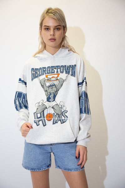 Grey sweater with a large Georgetown Hoyas spell-out across the front, the team mascot scoring a hoop, dated 1991 and Georgetown printed on both arms. Has a kangaroo-pouch style pocket and a hood.
