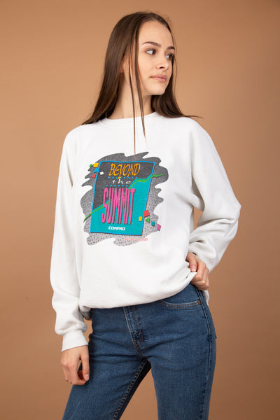 White with a 1990's colourful graphic and 'Beyond The Summit' printed across the front.  Dated January 24, 1995. The neckline is stretched out, adding to the baggy fit.