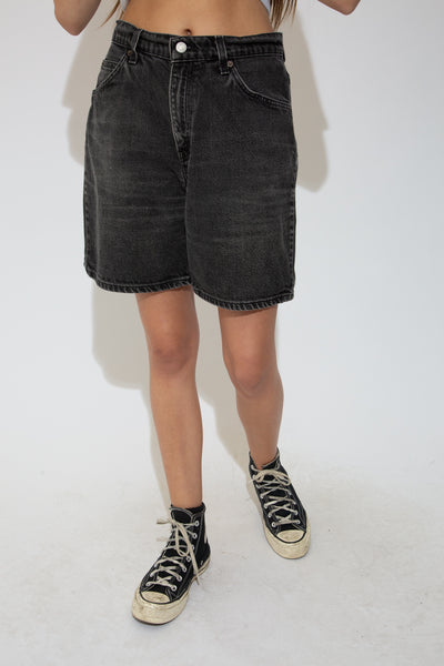 Black denim shorts with black stitching, a mid-length, relaxed fit and Levis branding on the back waistline, back pocket, button and domes.