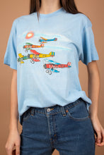 Load image into Gallery viewer, This light blue tee is a soft, loose-fitting top with an aeroplane graphic on the front. Single-stitch and dated '88, this is a vintage must-have.
