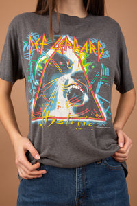 This single-stitch grey tee has a colourful 80's print of a screaming man and a triangle on the front. 'Def Leppard Hysteria' is written across in red and yellow. On the back is a list of their 'Hysteria' tour locations.