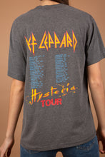 Load image into Gallery viewer, This single-stitch grey tee has a colourful 80's print of a screaming man and a triangle on the front. 'Def Leppard Hysteria' is written across in red and yellow. On the back is a list of their 'Hysteria' tour locations.