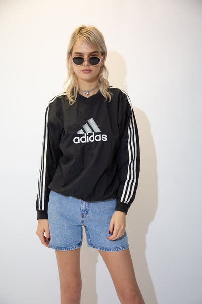 Black in colour in an anorak, rain jacket material, this sweater has a large Adidas spell-out across the front with the signature three striped sone the sleeves.
