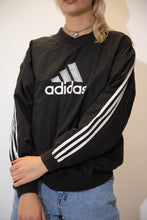 Load image into Gallery viewer, Black in colour in an anorak, rain jacket material, this sweater has a large Adidas spell-out across the front with the signature three striped sone the sleeves.
