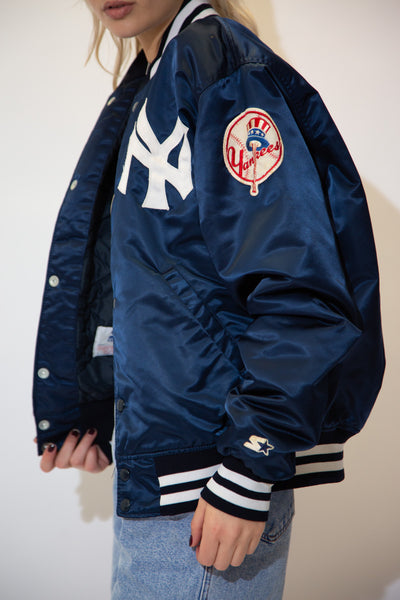 Navy blue in colour with a striped collar, waistline and sleeves, this bomber style jacket has the iconic interlinking NY logo on the left chest and the OG Yankees logo on the left sleeve.