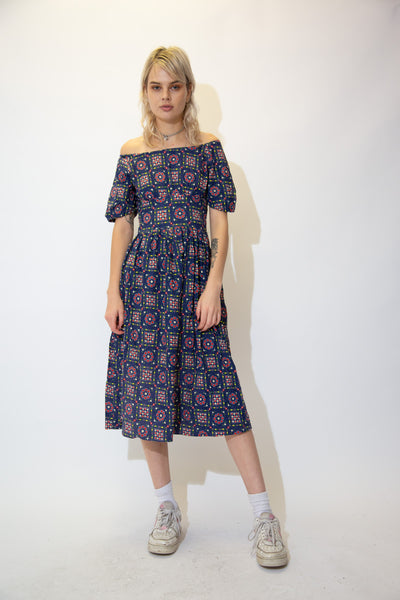 Navy blue in colour with a colourful abstract print of hearts and flowers across the front and back, this dress is in a midi-length style with an off-the-shoulder neckline.