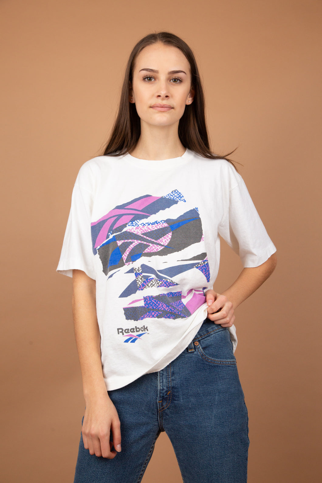 This white single-stitch top has a purple and blue 80's graphic on the front with 'Reebok' printed at the bottom and on the back. Neckline is slightly stretched out to add to vintage look.