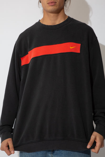faded black nike crew with red stripe detailing across chest and down the underside of left sleeve and yellow embroidered tick emblem on left chest