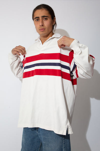 white rugby with red and navy strriped detailing across chest and sleeves