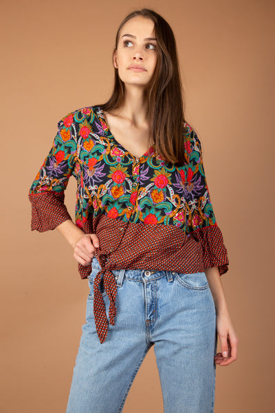 This colourful button-up blouse is halved horizontally by two contrasting patterns - a floral pattern and a dotted diamond pattern. With flared arms and a tie-around waist, this is a summer must-have.