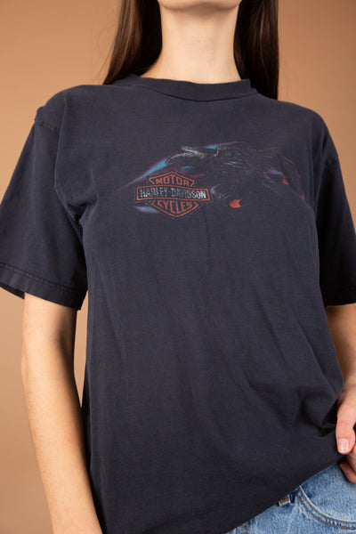 This Harley Davidson Tee is thick and faded black. On the front, a faded eagle print with the Harley Davidson logo. On the back, a large eagle print with orange 'Black Hills Rapid City, SD' writing.