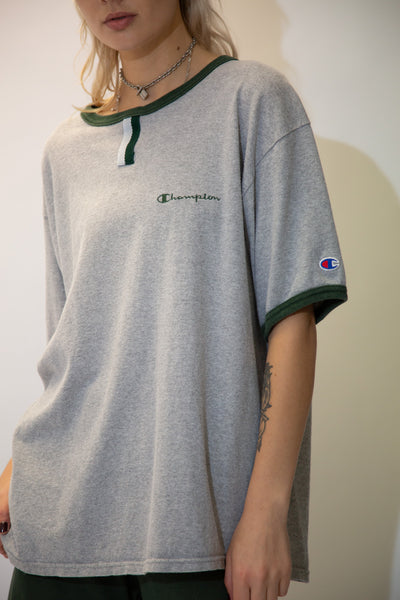 Grey in colour, this tee has green rimmed along the neckline and sleeves, a vertical strip on the neckline and Champion branding on the left chest and left sleeve.