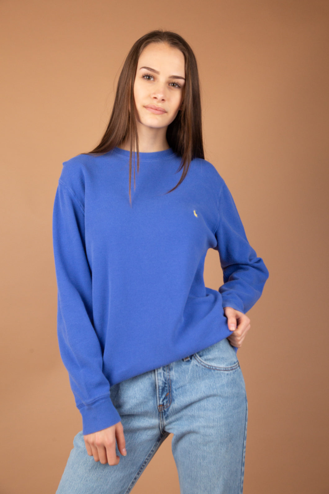 This ribbed sweater is cornflower-blue with the yellow Polo Ralph Lauren logo on the left breast. The collar is slightly stretched out, adding to the baggy fit.