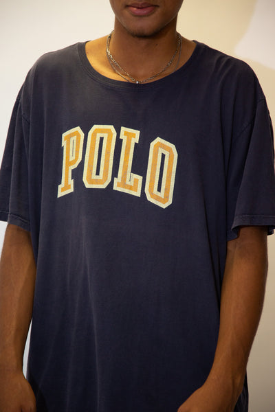 the model wears a navy tee with a polo spell out on the front