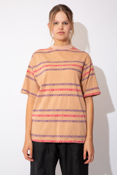 "tan coloured tee with horizontal stripes in pink and purple that say ""Hang Ten"" and have little feet."