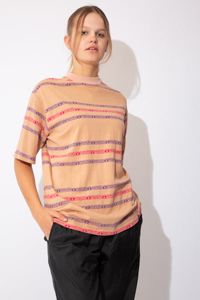 tan coloured tee with horizontal stripes in pink and purple that say