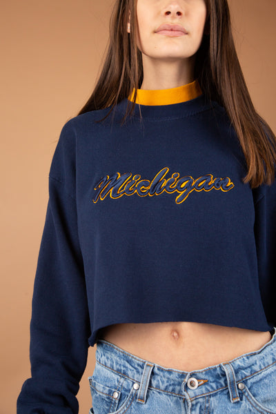 This Michigan sweater is navy blue in colour with a layered polo neck in contrasting colours. Navy blue and yellow embroidery of 'Michigan' across the front and cropped to keep it cute.