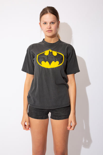 Model is wearing a faded black tee that features the Batman logo on the front center, this tee is also single stitch