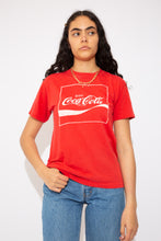Load image into Gallery viewer, This tee is red, with the Coca-Cola logo on the front. On the back, 'Have a coke and a smile. Coke adds life.' Ribbed crew neckline adds to the fitted style of the tee.