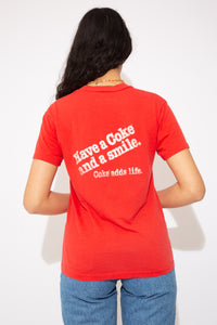 This tee is red, with the Coca-Cola logo on the front. On the back, 'Have a coke and a smile. Coke adds life.' Ribbed crew neckline adds to the fitted style of the tee.