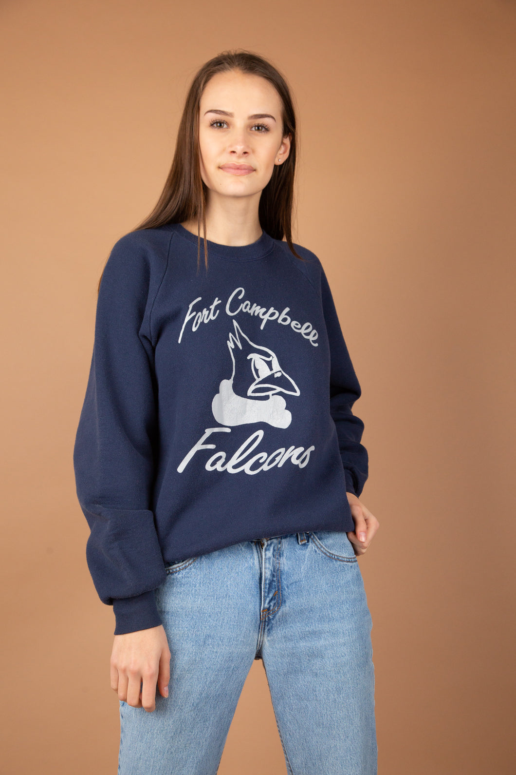 Navy blue in colour with a grey print on the front of a falcon head. 'Fort Campbell Falcons' printed on the front. Has stretched out neckline with ribbed sleeves, neckline and waistline.