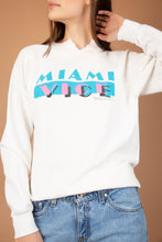 Load image into Gallery viewer, White vintage sweater with a pink and blue 80s print of 'Miami Vice' on the front. Dated 1984 with a 'V' intentionally cut on neckline.