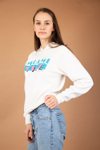 White vintage sweater with a pink and blue 80s print of 'Miami Vice' on the front. Dated 1984 with a 'V' intentionally cut on neckline.