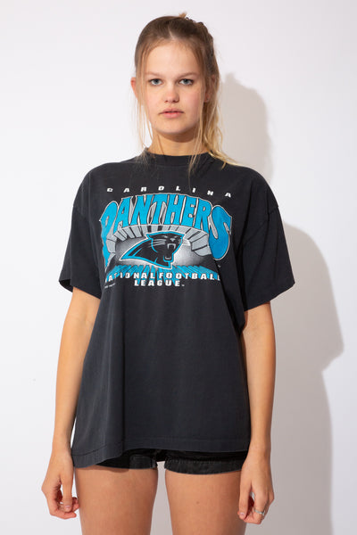 The model is wearing a faded black Carolina Panthers tee that fits slightly oversized on the model