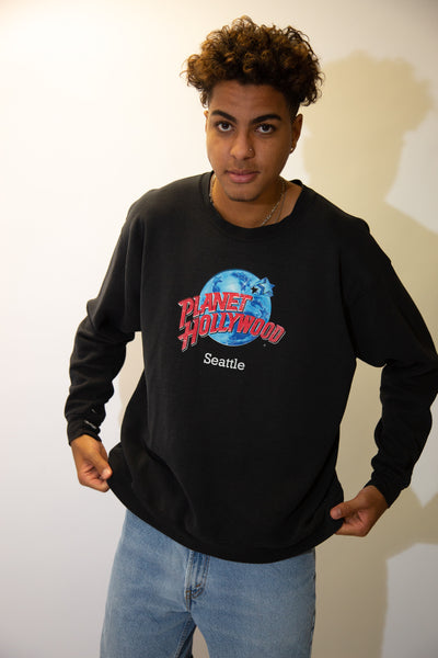 the model wears a black sweater with a planet hollywood graphic on the front