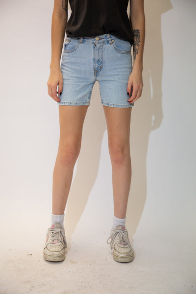 Light-wash blue in colour, these shorts are in a midi-length style, have brown stitching, pentagon shaped back pockets and Calvin Klein branding on the buttons, domes, right front pocket and back waistline.