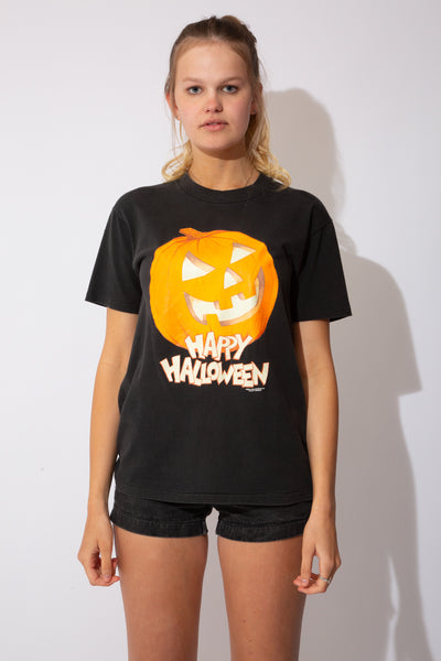 The model is wearing a thick black tee that features a carved pumpkin on the front with the words 'Happy Halloween' down the bottom