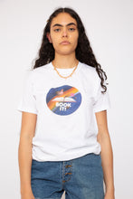 Load image into Gallery viewer, model is wearing a crisp white tee that features a awesome 90s aesthetic print on the front which has the words Book It!