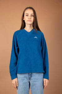 This Adidas cobalt blue sweater is a thick fleece-like material with a ribbed v-neck and light blue and white Adidas logo on the left chest.