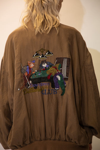 Brown in colour with a silky feel, this bomber style jacket has an appliqué of a tiger, a bear and a crocodile playing a game of billiards on the back. 'Downtown Billiards Club' spell-out below.