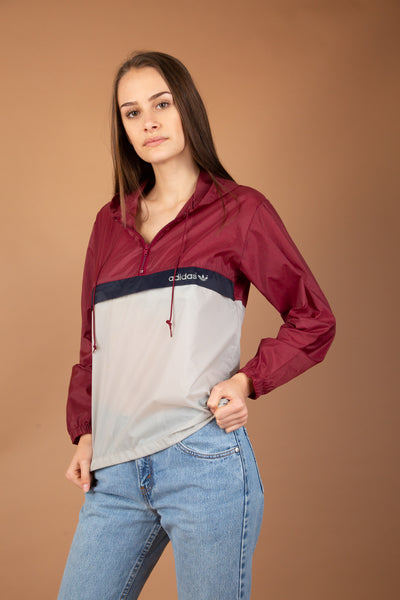 This Adidas Pullover is maroon red, navy blue and mushroom grey. Finished of with a quarter-zip, a hood and drawstrings along the neckline and waistline. With rainjecket-like material, this is a vintage must-have.